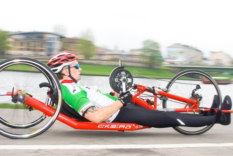 КРАКОВ, ПОЛЬША - 28-ОЕ АПРЕЛЯ: Марафонцы человека Cracovia Marathon.Handicapped в кресло-коляске на улицах города стоковое изображение rf