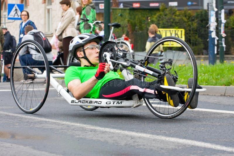 КРАКОВ, ПОЛЬША - 28-ОЕ АПРЕЛЯ: Марафонцы человека Cracovia Marathon.Handicapped в кресло-коляске на улицах города стоковые фотографии rf
