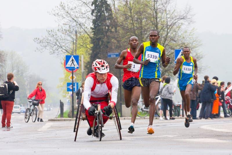 КРАКОВ, ПОЛЬША - 28-ОЕ АПРЕЛЯ: Марафонцы человека Cracovia Marathon.Handicapped в кресло-коляске на улицах города стоковое фото rf