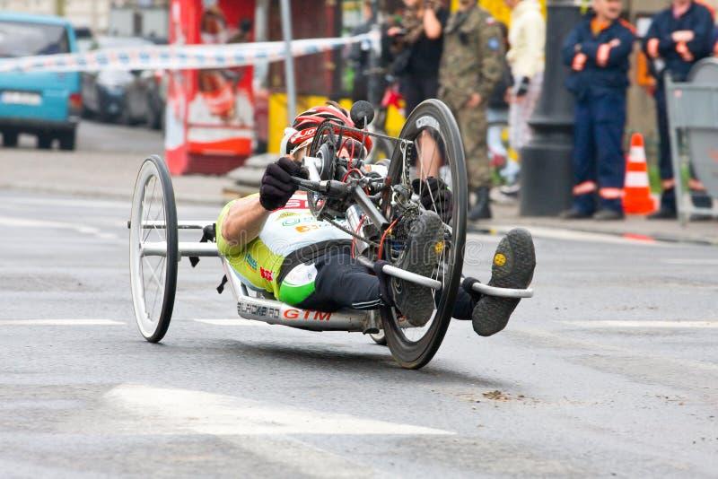 КРАКОВ, ПОЛЬША - 28-ОЕ АПРЕЛЯ: Марафонцы человека Cracovia Marathon.Handicapped в кресло-коляске на улицах города стоковая фотография