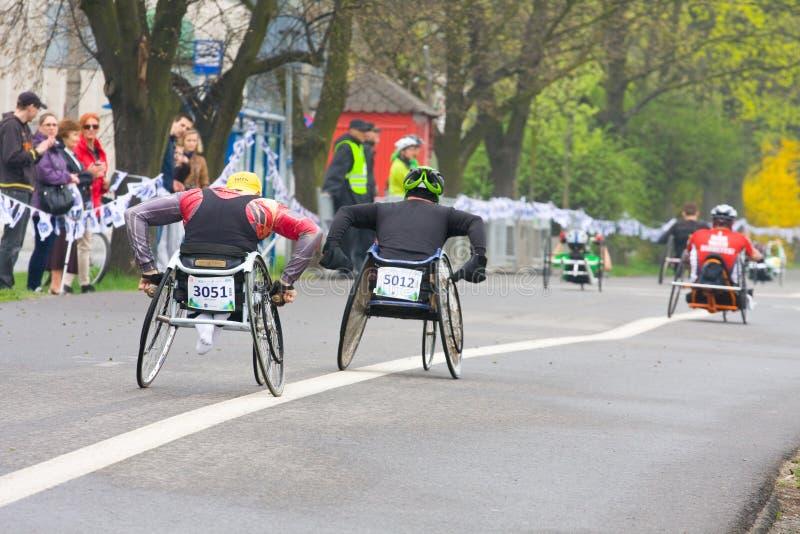 КРАКОВ, ПОЛЬША - 28-ОЕ АПРЕЛЯ: Марафонцы человека Cracovia Marathon.Handicapped в кресло-коляске на улицах города стоковые изображения