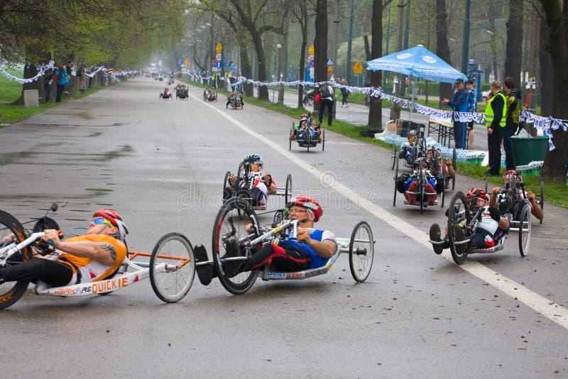 КРАКОВ, ПОЛЬША - 28-ОЕ АПРЕЛЯ: Марафонцы человека Cracovia Marathon.Handicapped в кресло-коляске на улицах города стоковые изображения rf