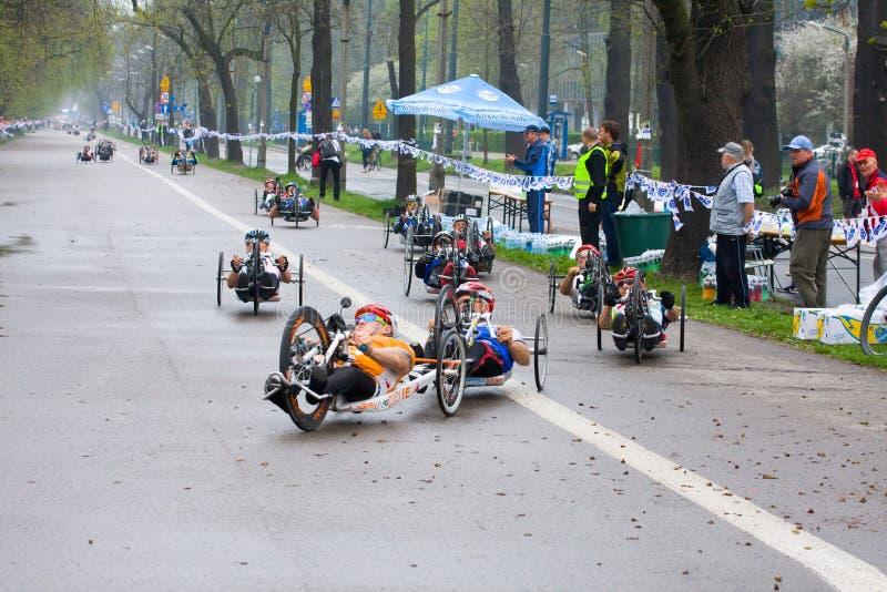 КРАКОВ, ПОЛЬША - 28-ОЕ АПРЕЛЯ: Марафонцы человека Cracovia Marathon.Handicapped в кресло-коляске на улицах города стоковое фото