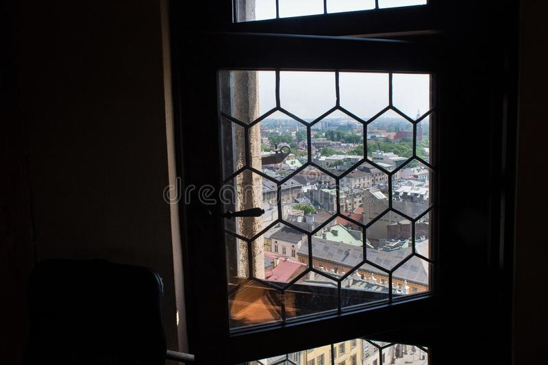 КРАКОВ, ПОЛЬША - 29-ОЕ МАЯ 2016: Взгляд через старое пылевоздушное окно в башне базилики ` s St Mary стоковые изображения