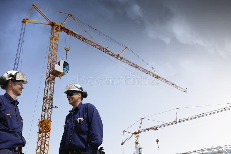 Краны конструкции и работники здания стоковые фотографии rf