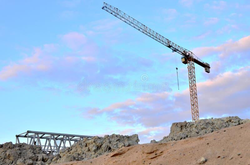 Кран башни конструкции кливера и новые жилые дома на строительной площадке на предпосылке захода солнца и голубого неба стоковые изображения