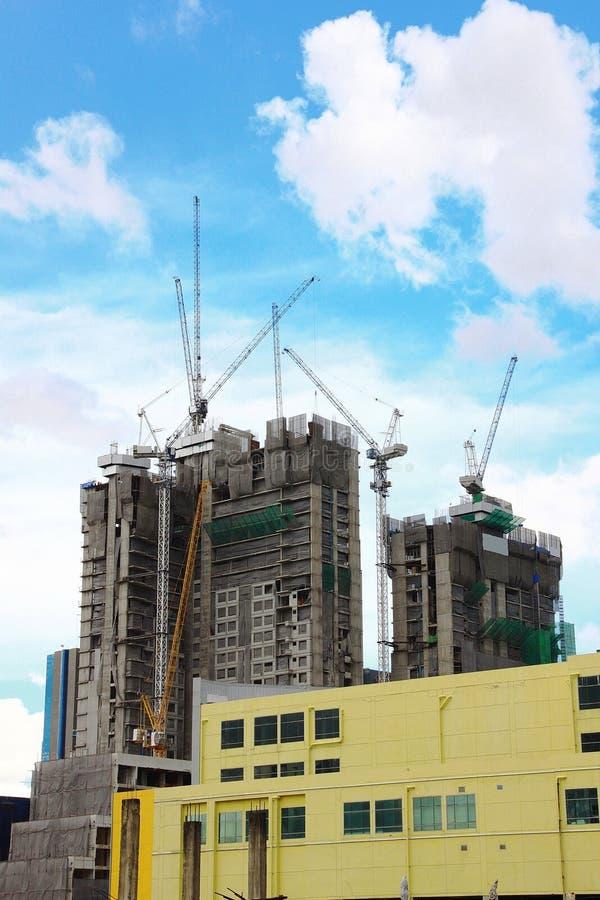Кран башни Highrise и новый незаконченный жилой таунхаус под конструкцией, желтым вид спереди здания и предпосылка неба стоковые фотографии rf