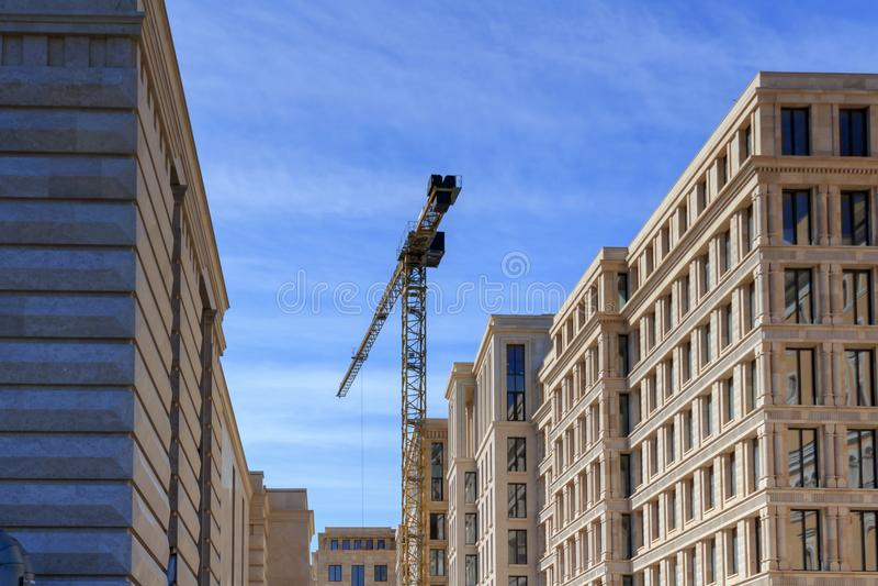 Кран высотного здания на предпосылке домов под конструкцией стоковые изображения