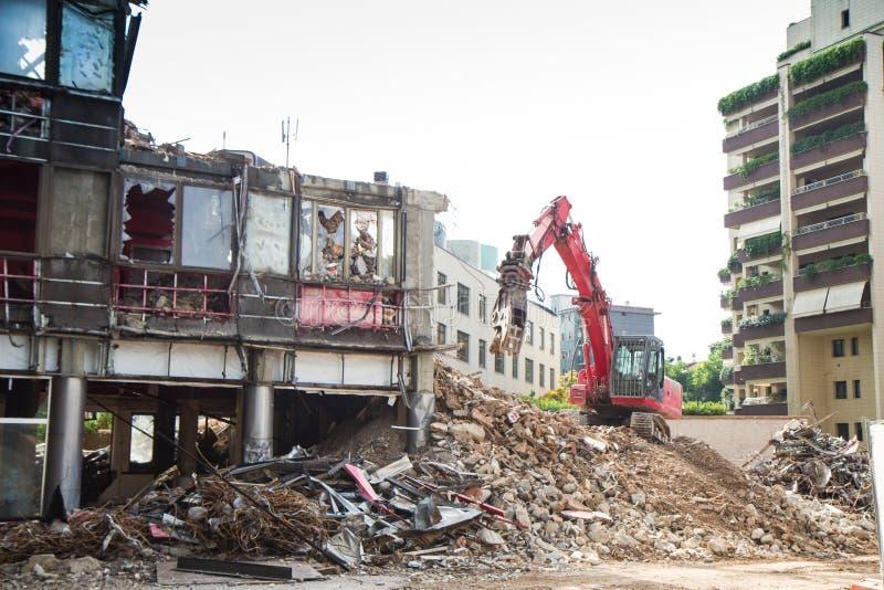 Кран и землекоп работая на подрывании здания стоковые фотографии rf