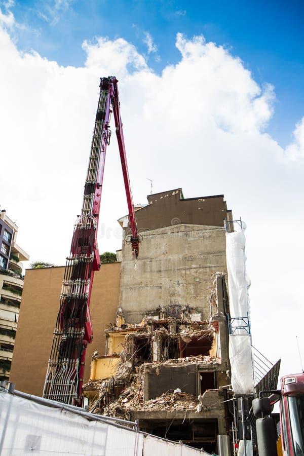 Кран и землекоп работая на подрывании здания стоковое фото