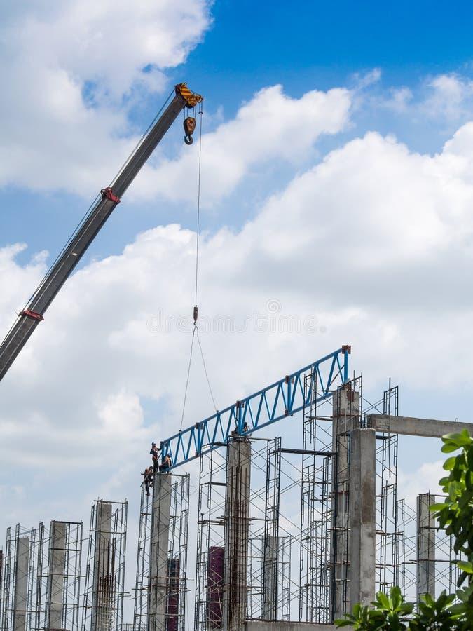 Кран и работники на строительной площадке и голубом небе стоковое фото rf