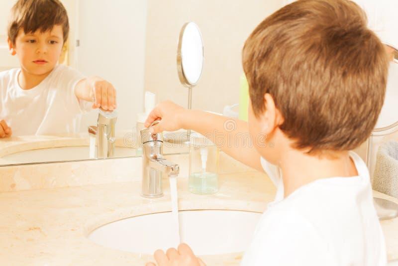 Кран кавказского мальчика ребенк поворачивая дальше в ванной комнате стоковое изображение
