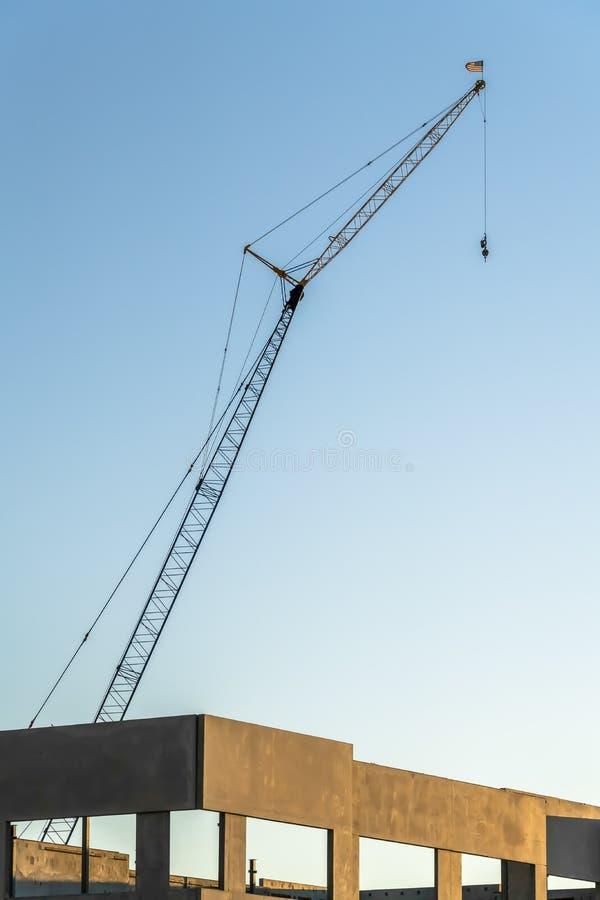 Кран конструкции возвышаясь над конкретными рамками незаконченного здания стоковая фотография rf