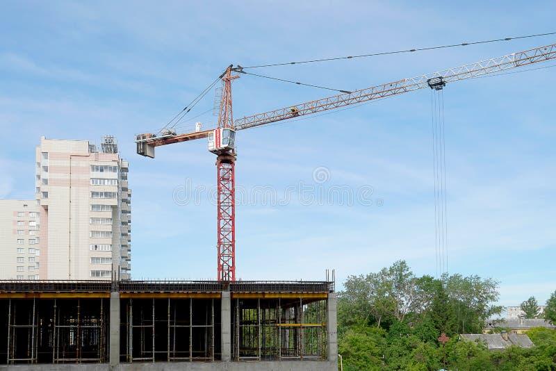 Кран конструкции поднимает инструмент работы Кран заграждения на конструкции многоэтажного здания Голубое небо, леса стоковые фотографии rf
