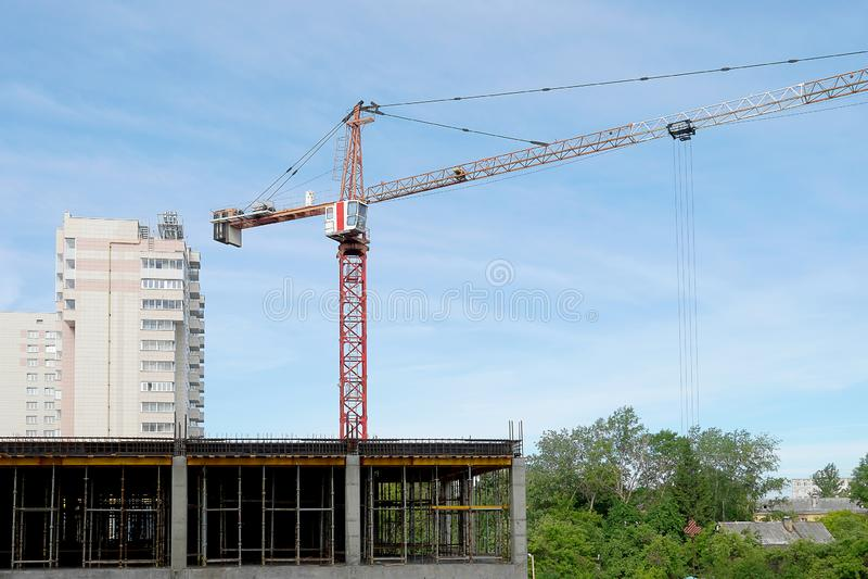 Кран конструкции поднимает инструмент работы Кран заграждения на конструкции многоэтажного здания Голубое небо, леса стоковая фотография