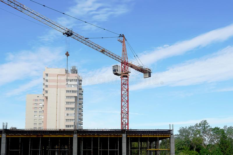 Кран конструкции транспортирует инструмент Кран заграждения на конструкции многоэтажного здания Голубое небо, леса стоковая фотография