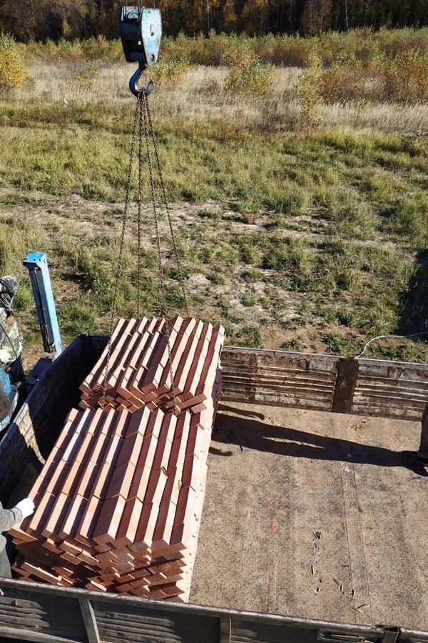 Кран тележки разгружает кирпичи для построения дома стоковые изображения rf