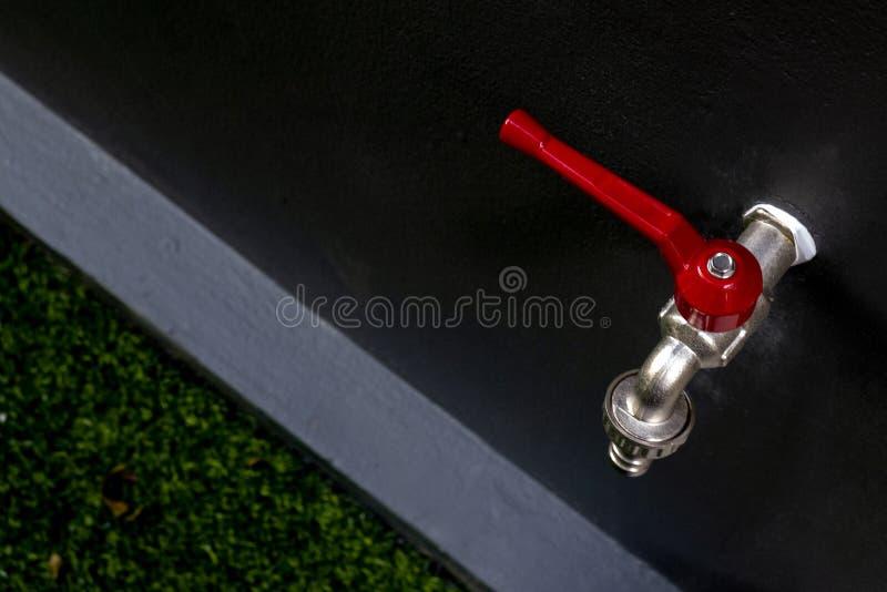 Кран faucet воды в красном цвете на стене в сером цвете bathroom темном стоковые изображения
