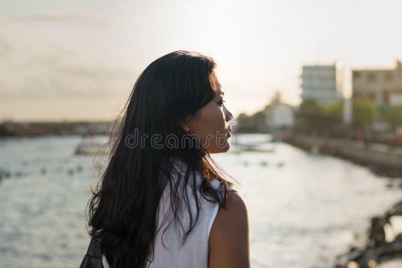 Красивая азиатская дама около океана во время захода солнца стоковые фотографии rf