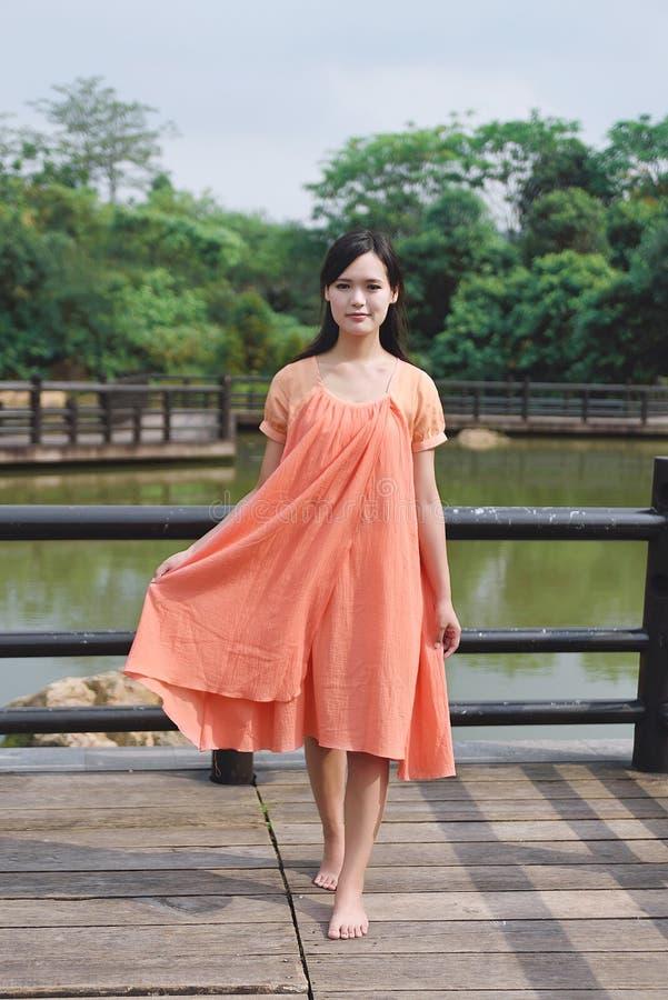 Красивая азиатская девушка одела в традиционном платье элементов показывая стоковое изображение