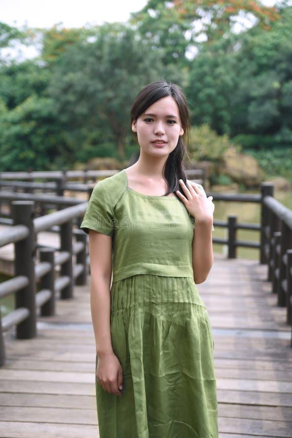Красивая азиатская девушка одела в традиционном платье элементов показывая стоковая фотография rf