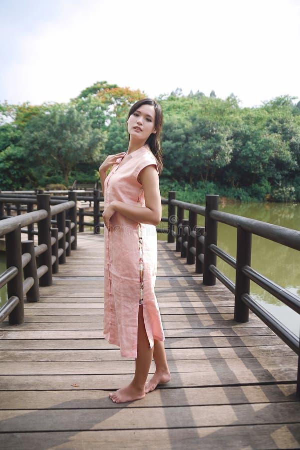 Красивая азиатская девушка одела в традиционном платье элементов показывая стоковое изображение rf