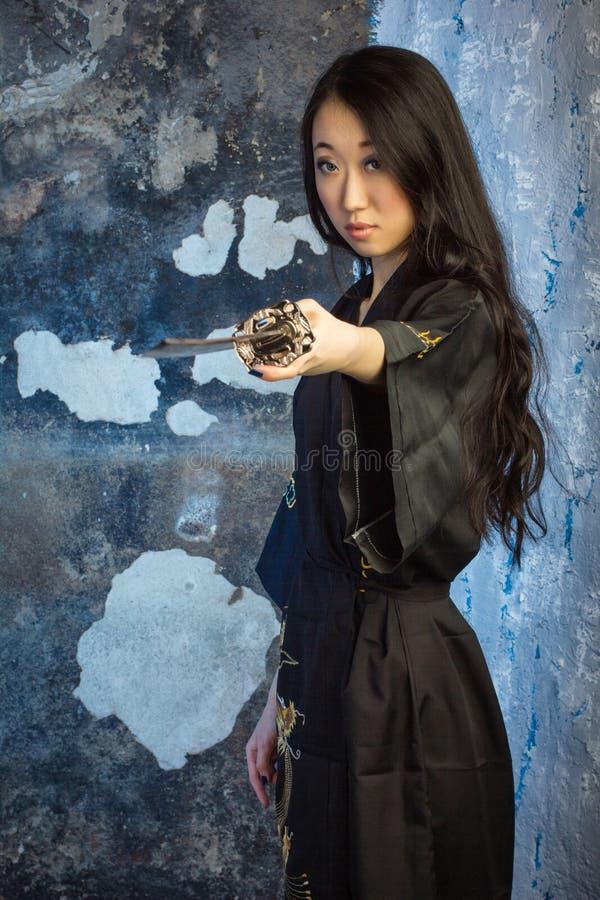 Красивая азиатская девушка в кимоно с katana стоковые изображения