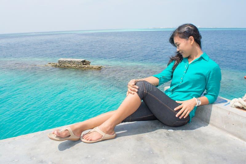 Красивая азиатская девушка сидя на верхней части и смотря вниз на океане стоковое изображение rf