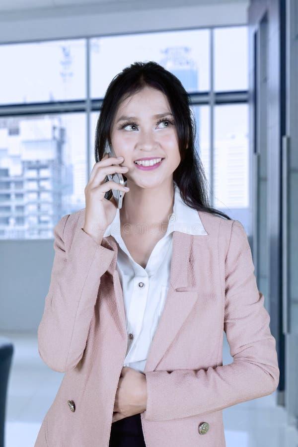 Красивая азиатская женщина говоря на телефоне на офисе стоковые фотографии rf