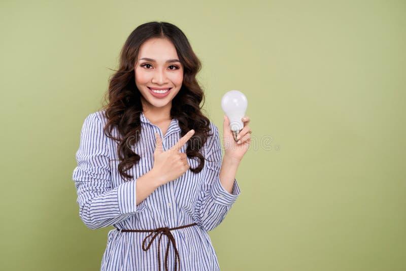 Красивая азиатская женщина держа и указывая электрическую лампочку стоковые фото