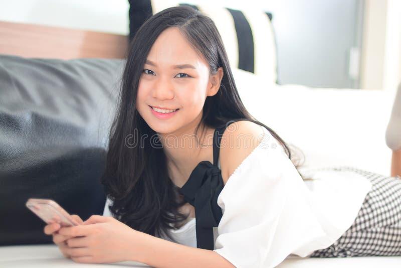 Красивая азиатская женщина имеет smartphone на руках и улыбке стоковая фотография