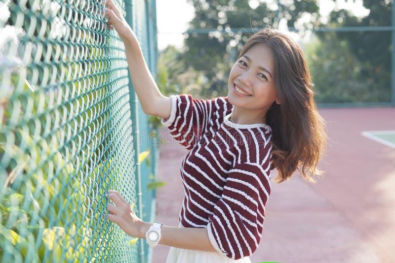 Красивая азиатская женщина ослабляя, каникулы счастья в spo тенниса стоковое фото rf