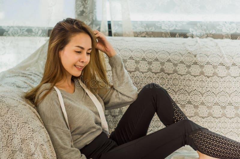 Красивая азиатская женщина отдыхая, на софе и счастливой улыбке в доме с релаксацией, концепция устанавливать цели для дела стоковое изображение