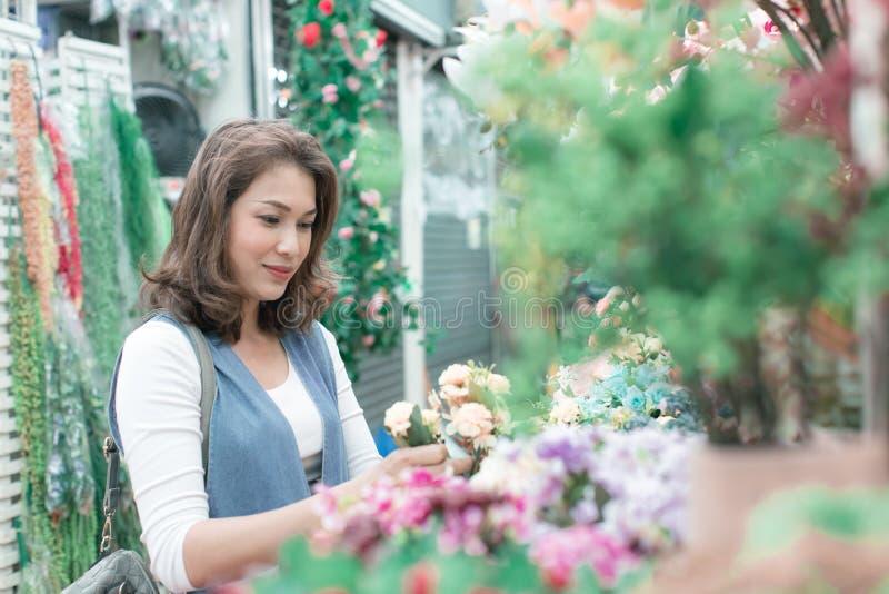 Красивая азиатская женщина покупает цветки счастливо от цветка стоковое изображение rf