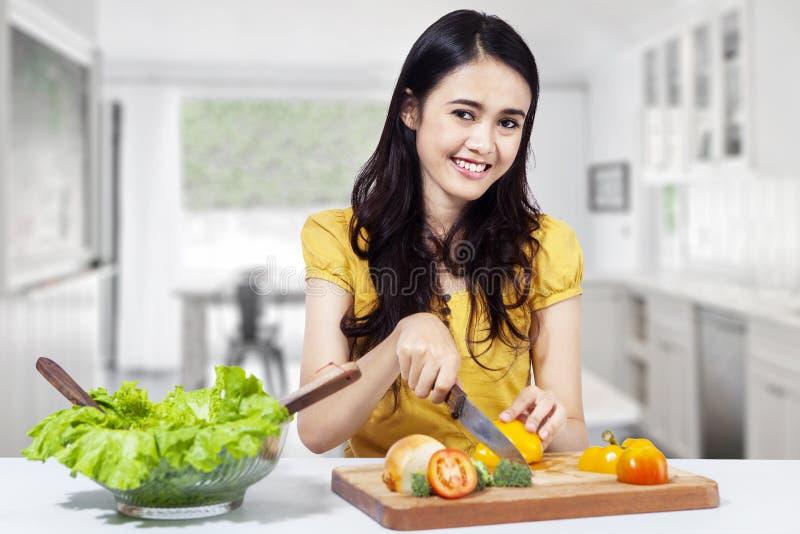 Красивая азиатская женщина подготавливает салат стоковая фотография rf
