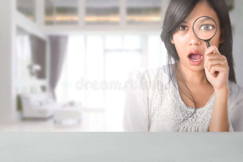 Красивая азиатская женщина смотря через лупу стоковое фото