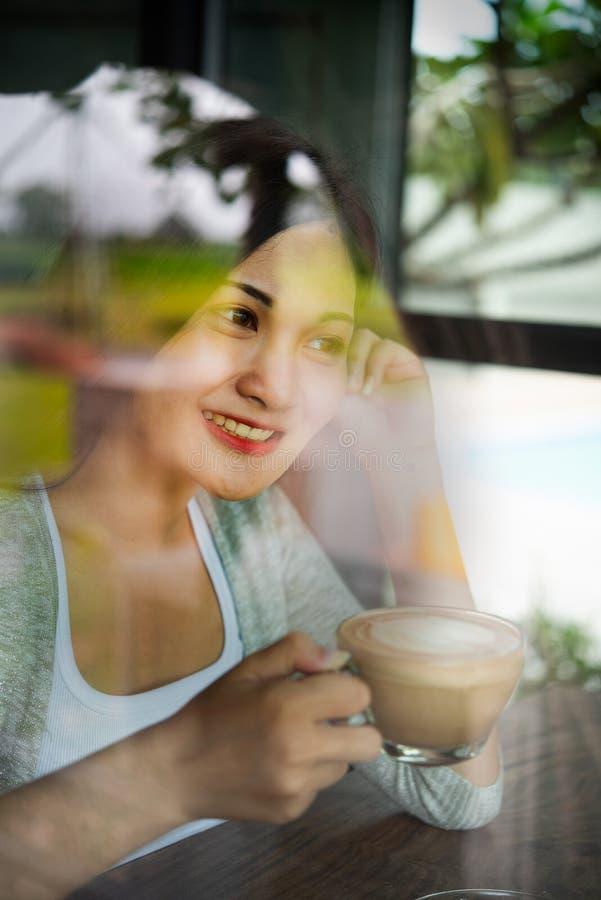 Красивая азиатская женщина усмехается счастливо с кофе в ресторане Образ жизни молодых женщин во время расслабляющего времени в стоковое изображение