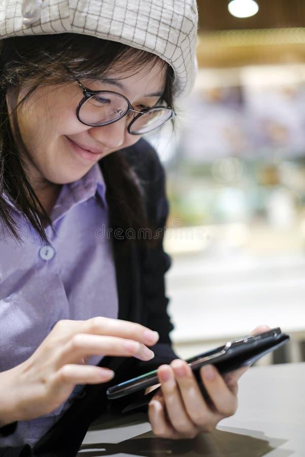 Красивая азиатская женщина усмехаясь и используя мобильный телефон стоковые изображения rf