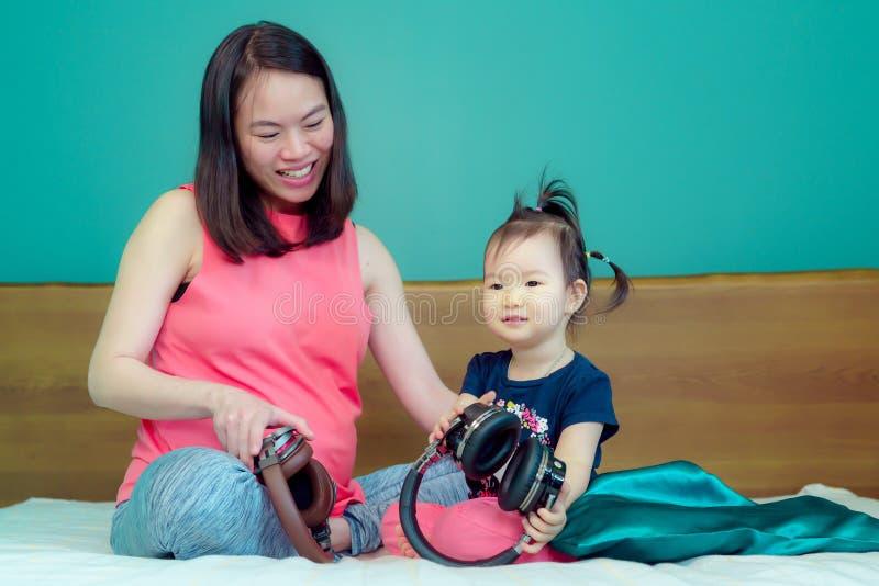 Красивая азиатская мать дамы беременна Примите большой приведенный шлемофон к животу позвольте ребенку в животе слушайте имейте м стоковые изображения