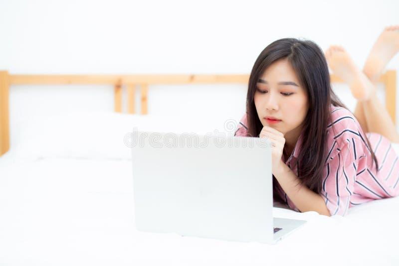 Красивая азиатская молодая женщина лежа на кровати используя ноутбук на спальне для отдыха и ослабить, работает не по найму с тет стоковое изображение