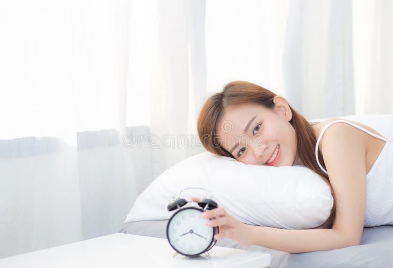 Красивая азиатская молодая женщина поворачивает будильник в утре, бодрствовании вверх для сна с будильником стоковое изображение