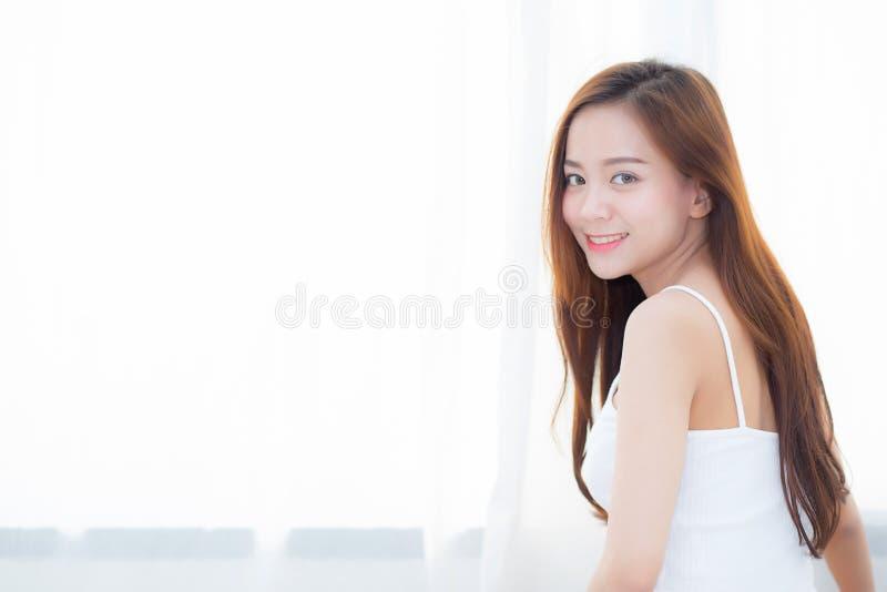Красивая азиатская молодая женщина усмехаясь при отдых счастья сидя на кровати дома окном стоковые фотографии rf