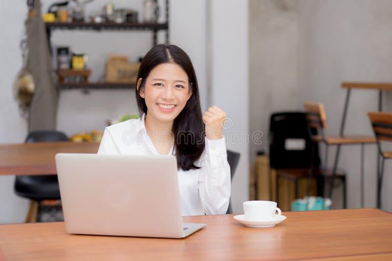 Красивая азиатская молодая коммерсантка возбужденная и радостная успеха с компьтер-книжкой стоковое фото rf
