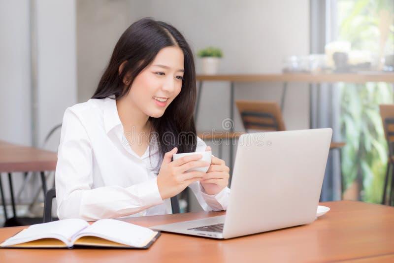 Красивая азиатская работа молодой женщины онлайн на компьтер-книжке сидя на кофейне стоковое фото rf