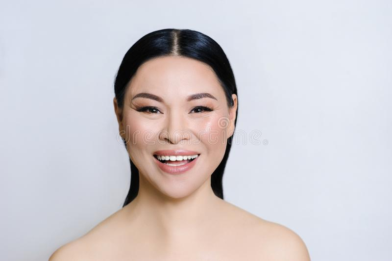 Красивая азиатская сторона женщины с чистой свежей кожей, обнаженным макияжем, косметологией, здравоохранением, красотой и спа стоковое изображение