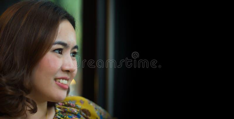 Красивая азиатская улыбка женщины и видит что-то с черной предпосылкой и копирует космос для текста стоковое изображение rf
