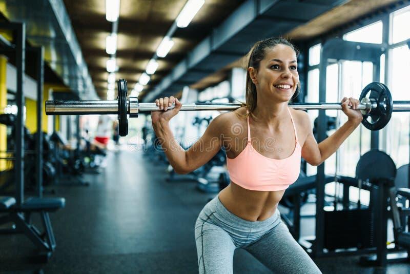 Красивая активная женщина делая сидения на корточках в спортзале стоковая фотография