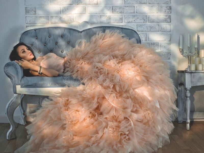 Красивая дама в шикарных ателье мод одевает на софе стоковая фотография