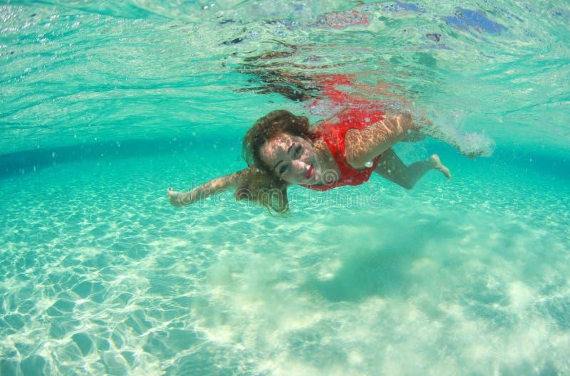 Красивая дама женщины в красном море воды платья заплыва стоковое фото