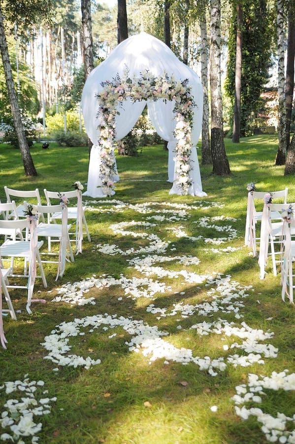 Красивая арка свадьбы Свод украшенный с белыми тканью и цветками стоковое изображение
